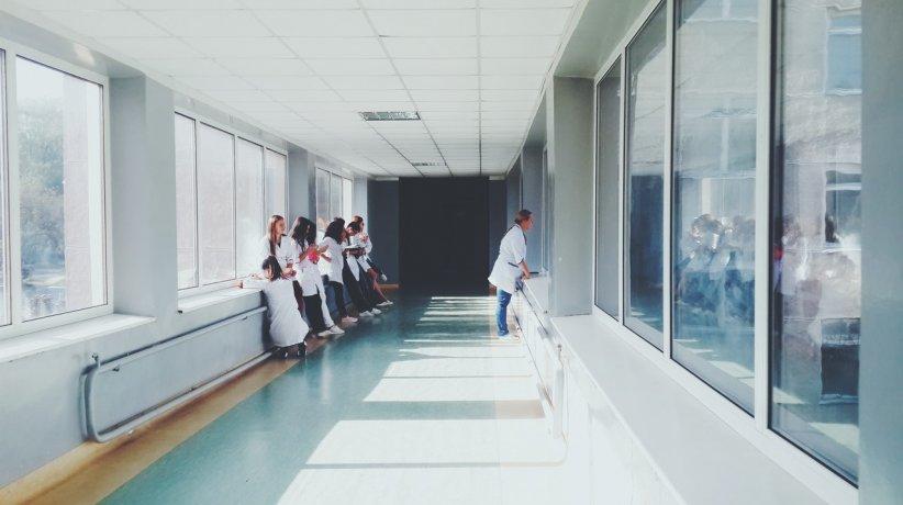 woman-in-white-shirt-standing-near-glass-window-inside-room-127873-1